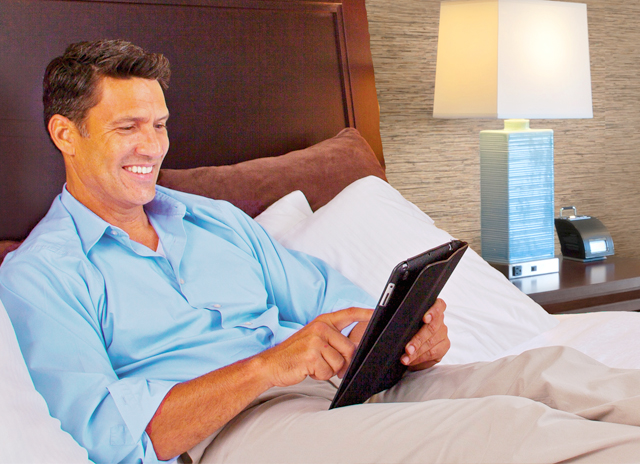 Man with tablet in Hotel Room Bed